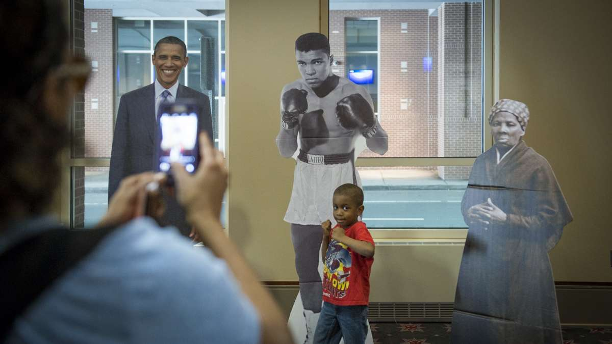 Isa Tawfeeq poses for a photo in front of cardboard cutouts of Muhammad Ali, Barack Obama, and Harriet Tubman at the Black History and Culture Showcase at the Pennsylvania Convention Center in Philadelphia. (Branden Eastwood for NewsWorks)