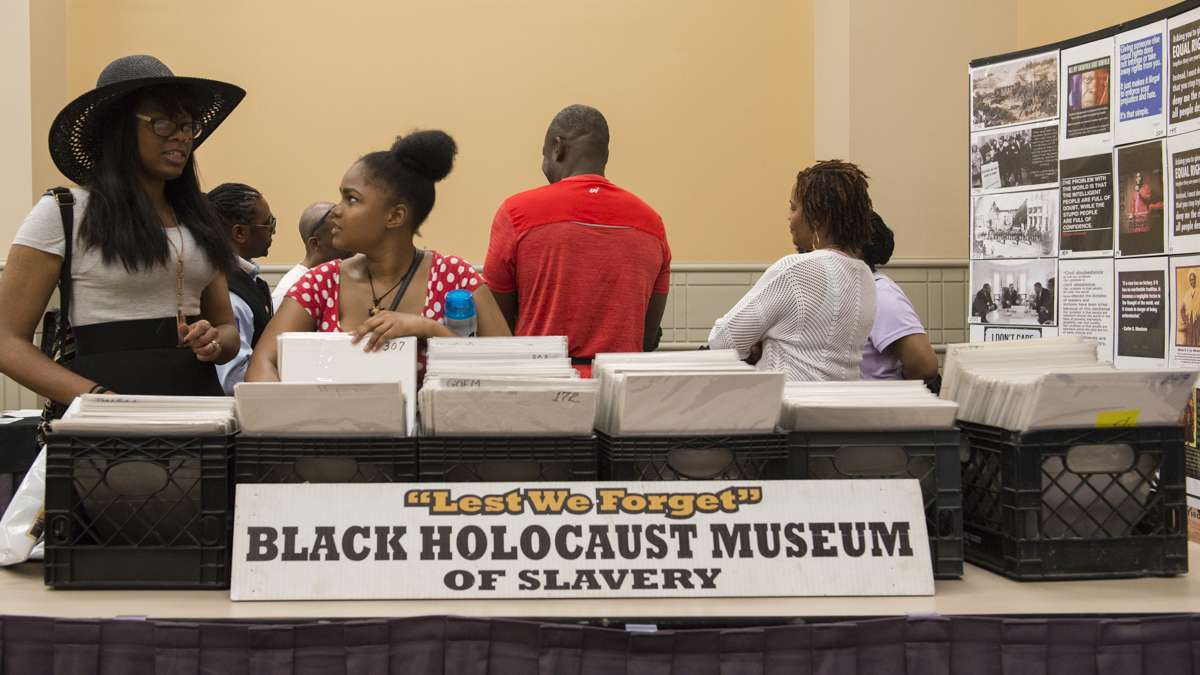 Malanna Simmons (left) speaks with friend Egypt Michelle while looking at prints from the Lest We Forget Black Holocaust Museum of Slavery. (Branden Eastwood for NewsWorks)