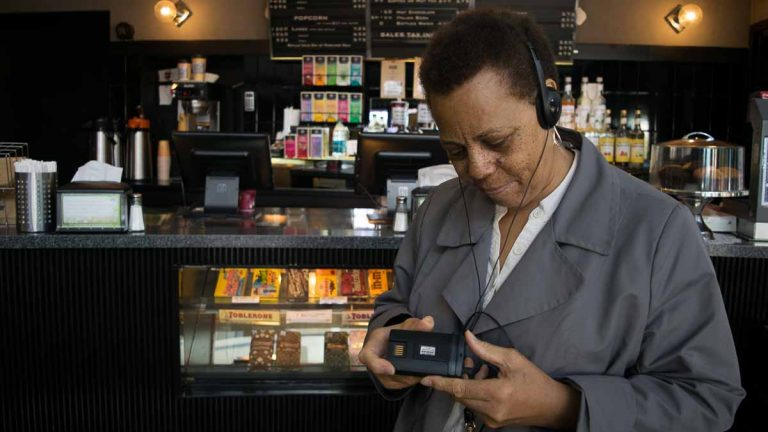 Sarita Kimble holds an audio description device at the Ritz Five movie theater in Philadelphia. (Paige Pfleger/WHYY)