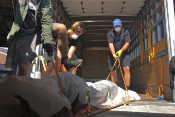 Movers spent Thursday transporting crumbling coffins and other excavated remains from temporary storage units to a central warehouse. (Elana Gordon/WHYY)