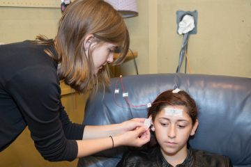 At the BrainVolts auditory neuroscience lab at Northwestern University a researcher places electrodes on a study participant's head to capture the electrical impulses created when we hear a sound. (Courtesy of Nina Kraus Northwestern University)