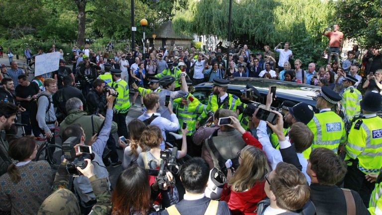 People gather around the car of British MP Boris Johnson