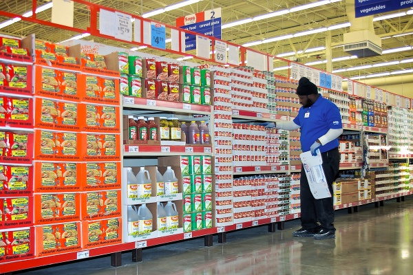 A Save-A-Lot employee places canned goods in Aisle 3. (Bas Slabbers/for NewsWorks)