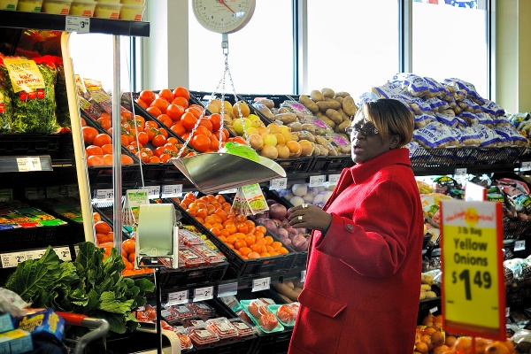 A customer weighs a head of lettuce in the produce aisle. (Bas Slabbers/for NewsWorks)