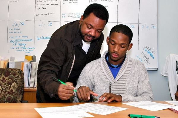 Vincent Booker signs along with his son Myles. (Bas Slabbers/for NewsWorks)