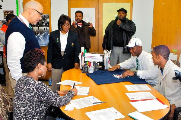 Will Parks's mother Nyerere signs paperwork that his father would immediately fax to the University of Arizona. (Bastiaan Slabbers/for NewsWorks)