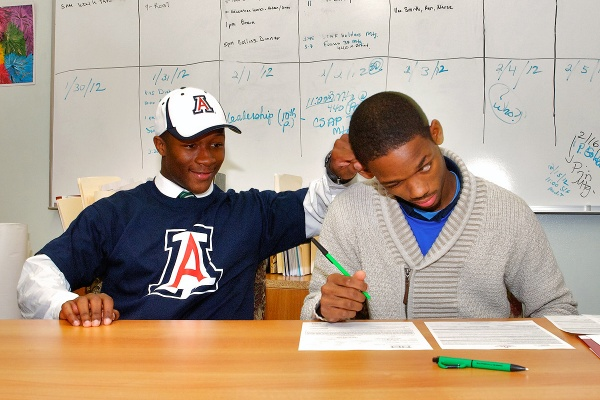 While signing his letter of intent to attend St. Francis University, Myles Brooker deals with an interruption from his friend since the age of six. (Bas Slabbers/for NewsWorks)