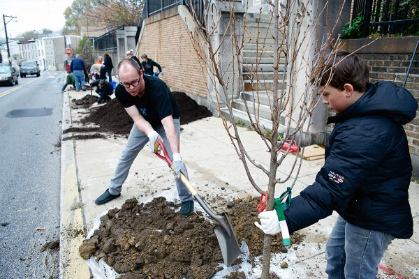 """<p><p>""""It is a good day for planting trees,"""" said J.D. Cramer. He and 10-year-old Landen Banks are working on one of the five trees. (Bas Slabbers/for NewsWorks)</p></p>"""