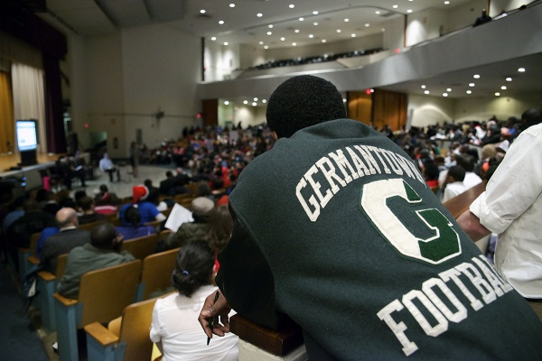<p><p>A man in a Germantown High football jacket looks over the crowd. The district's plan proposes that GHS students transfer move to Martin Luther King High or Roxborough High. (Bas Slabbers/for NewsWorks)</p></p>