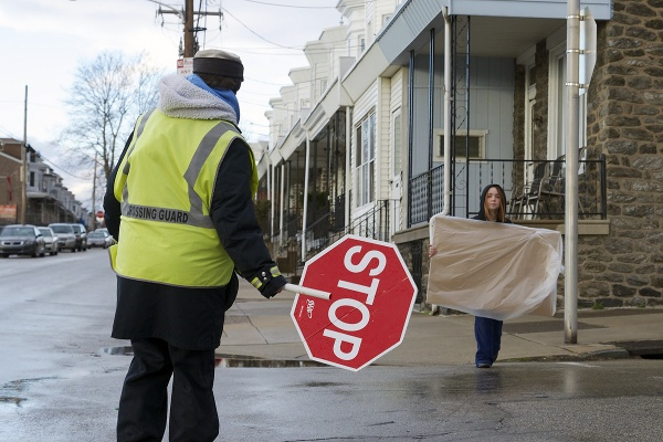<p><p>Chris Bartholomew blocks traffic for a young girl to cross the street with a school project. (Bas Slabbers/for NewsWorks)</p></p>