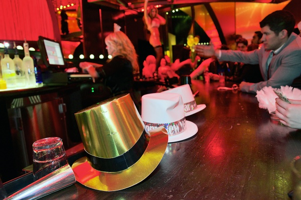 <p>New Years Eve themed hats lay on the bar of the Ivan Kane's Royal Jelly Burlesque Nightclub and in the background a performer dances for the patrons. (Bas Slabbers/for NewsWorks, file)</p>