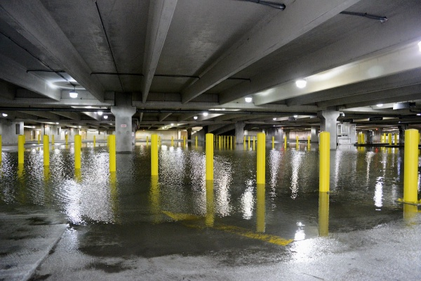 <p>4:30pm - Water stands in a parking garage under one of the casinos in AC. Pumps are deployed to get the water out.  (Bas Slabbers/for NewsWorks)</p>