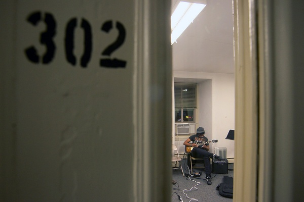 <p>Guitarist Darren Davis sits in room 302 of the Germantown Settlement Music School. (Bas Slabbers/for NewsWorks)</p>