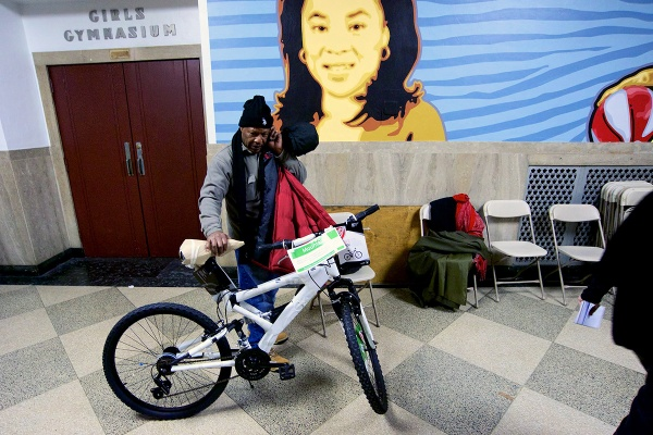 <p><p>A local resident holds the bicycle he won in Thursday night's raffle. (Bas Slabbers/for NewsWorks)</p></p>