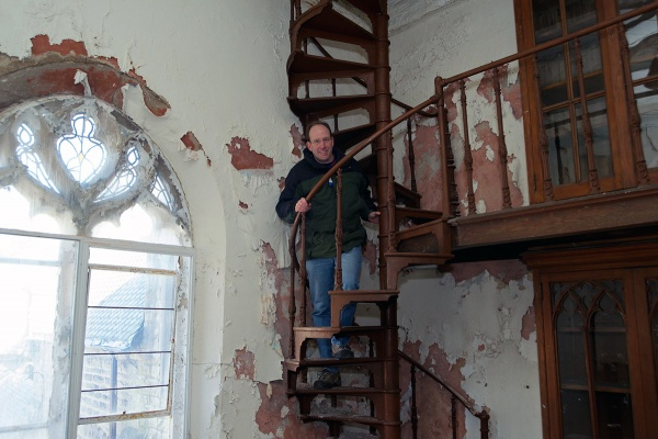 <p><p>Developer Ken Weinstein climbs a cast-iron staircase in the library. (Bas Slabbers/for NewsWorks)</p></p>