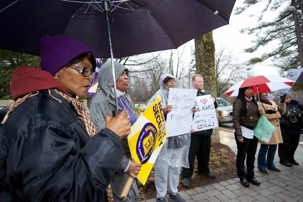 <p>Armed with umbrellas and protests signs a dozen security personal gathered on the corner of Henry Ave and School House Ln. (Bas Slabbers/for NewsWorks)</p>