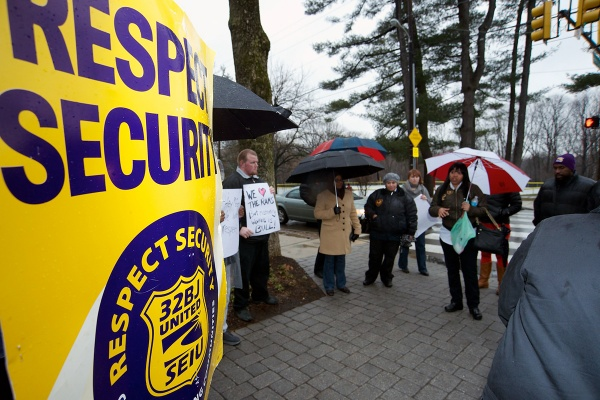 <p><p>Armed with umbrellas and protest signs, a dozen McGinn Security officers gathered on the corner of Henry Avenue and School House Lane to rally for better wages and working conditions. (Bas Slabbers/for NewsWorks)</p></p>