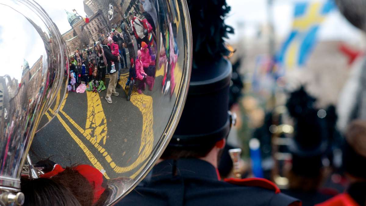 Crowds that line the parade route are seen reflected in one of the instruments of a marching band. (Bas Slabbers/for NewsWorks)