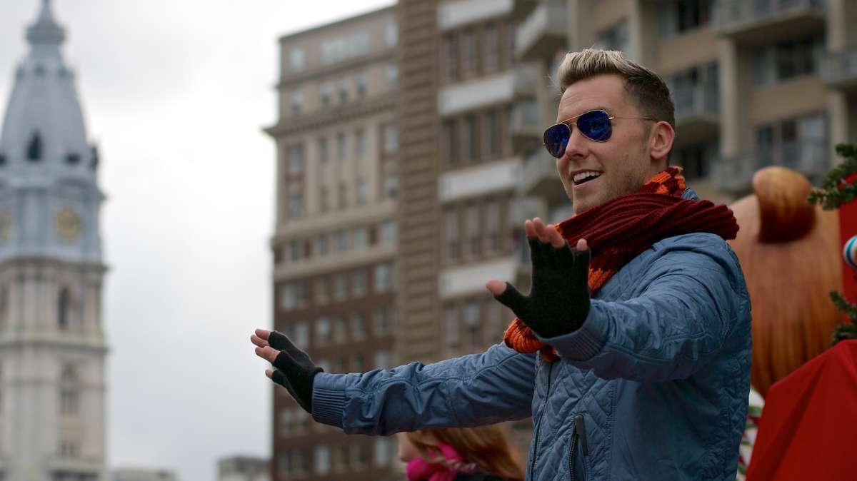 Former N'Sync member Lance Bass waves as he stands on the float that rides him down the Parkway. (Bas Slabbers/for NewsWorks)