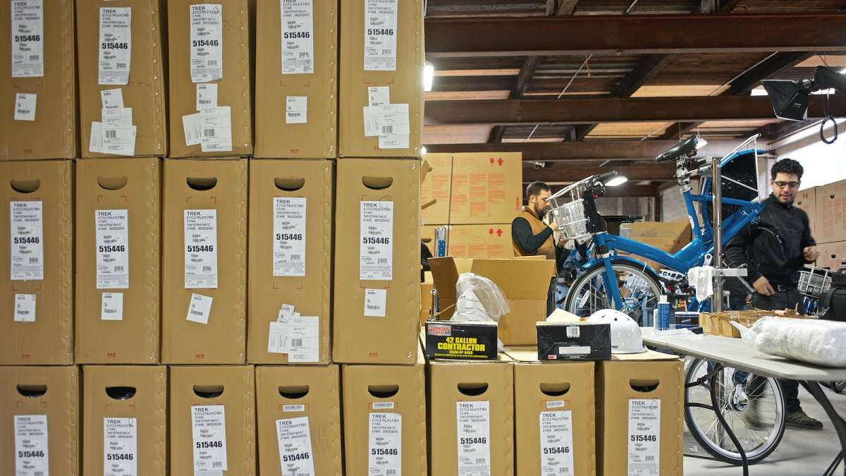 Hundreds of bikes in boxes wait to be assembled by a team of mechanics. (Bas Slabbers/for NewsWorks)