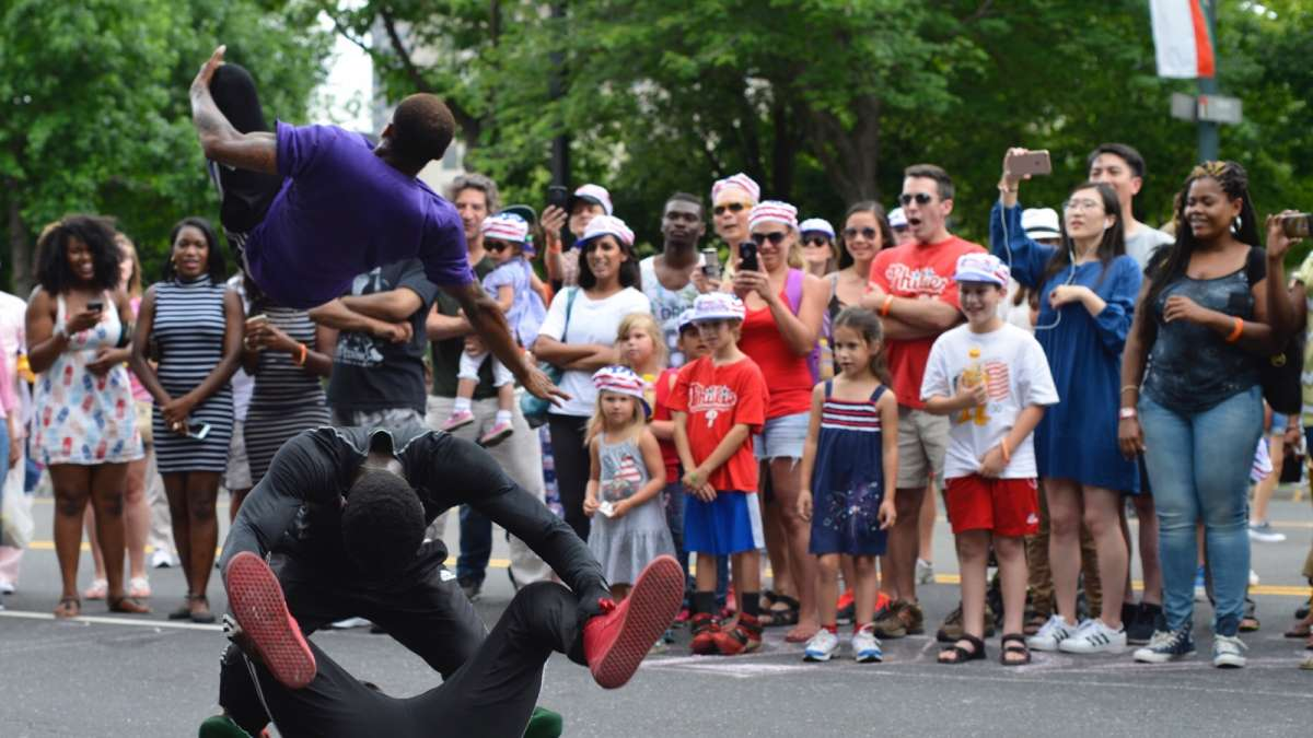 Najee Rose, with Inspired Visions United, entertains a crowd as he jumps over fellow performers on the Parkway.