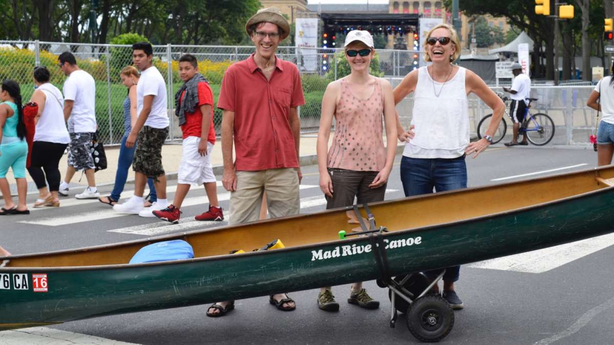 Paddlers Simon and Jean knight, with guest Susan Burrows, maneuver their canoe over the festival grounds heading to the Schuylkill River.