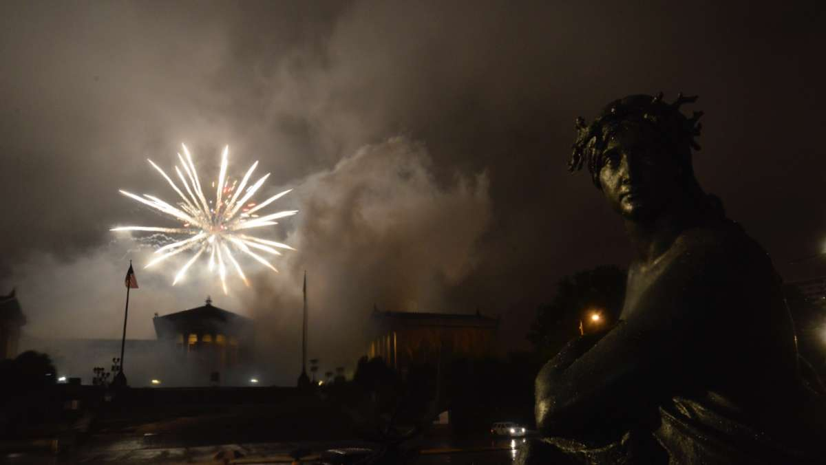 Rain and fog obscure the fireworks display at the art museum.