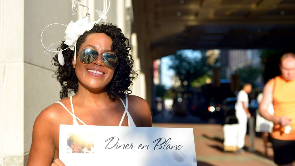 At one of the pickup locations, a hostess waits for a group participating in this year's Dîner en Blanc.