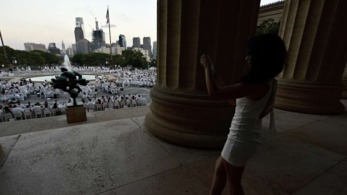 Courtney Yzzi makes a panoramic photo as she stands between the columns of the art museum.