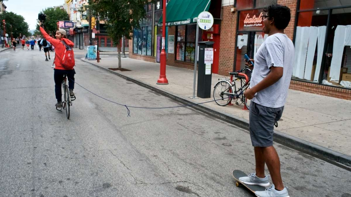 A skateboarder hitches a ride on South Street during Philly Free Streets day on Saturday.