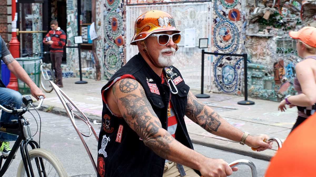 Mike ''Spin'' Spinelli, president of the Jersey Devils Bicycle Club, passes Isaiah Zagar's Magic Gardens as he rides with others on vintage and custom cruisers over South Street during the Philly Free Streets day.