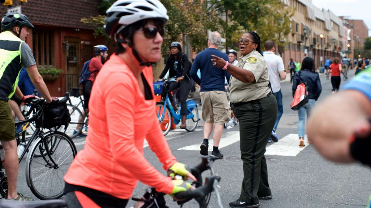 Javese Phelps-Washington, a Sanitation Enforcement Officer with the City, yells encouraging words to all the cyclists and runners at 21st and South streets.
