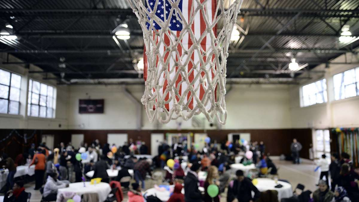 The hoops of the gym at the Old Pine Community Center are decorated with American flags as refugees take part in a Thanksgiving dinner on Sunday. (Bastiaan Slabbers for NewsWorks)