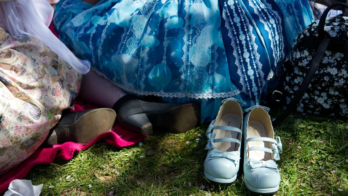 Dressed in Japanese fashion, members of Frilladelphia sit on the lawn under the sakura trees during the annual Cherry Blossom Festival in Fairmount Park on Sunday.