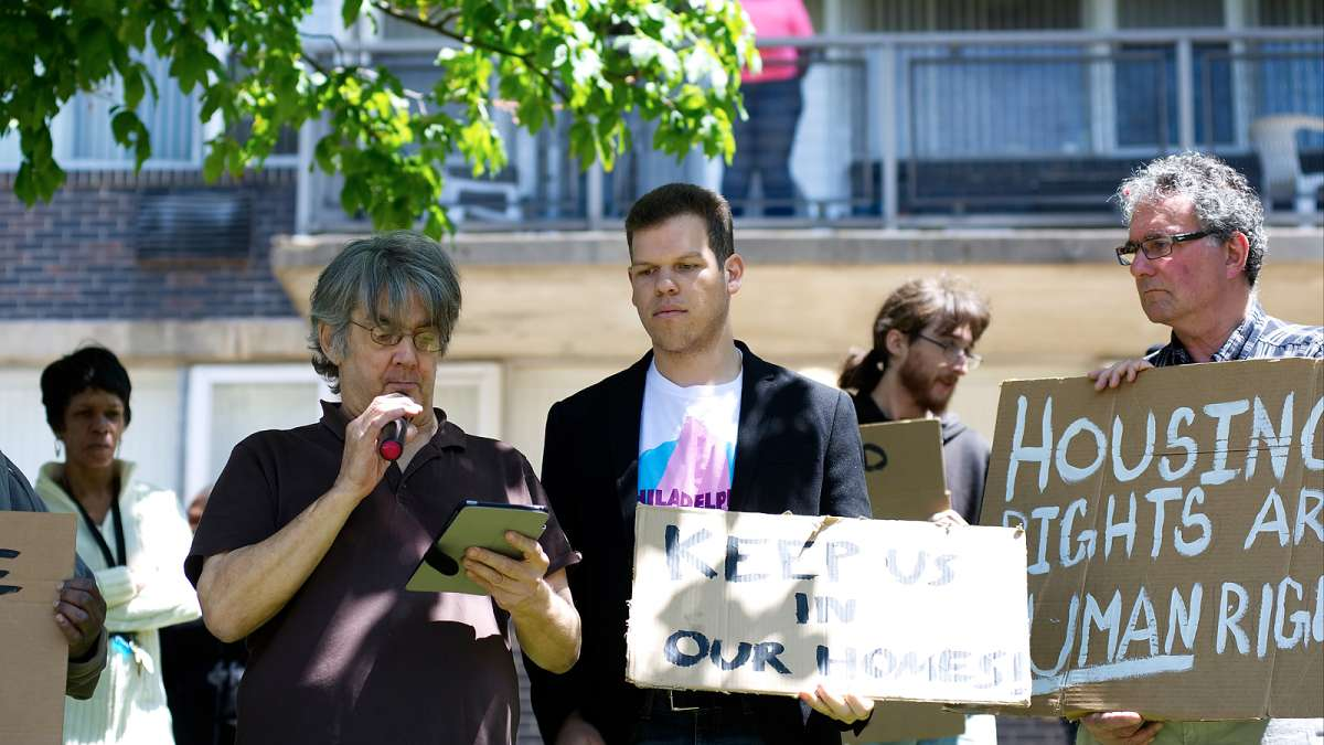Craig Cheney (center) reads a list of demands from the residents, during an anti-eviction rally outside Penn Wynn House, on Wednesday.