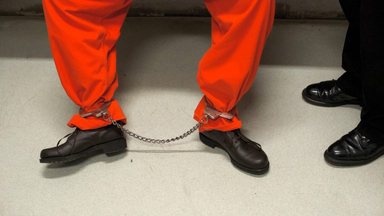 An inmate wearing a orange jumpsuit is seen chained up in the transition area that leads to the maximum security facility of the prison. (Bas Slabbers/for NewsWorks)