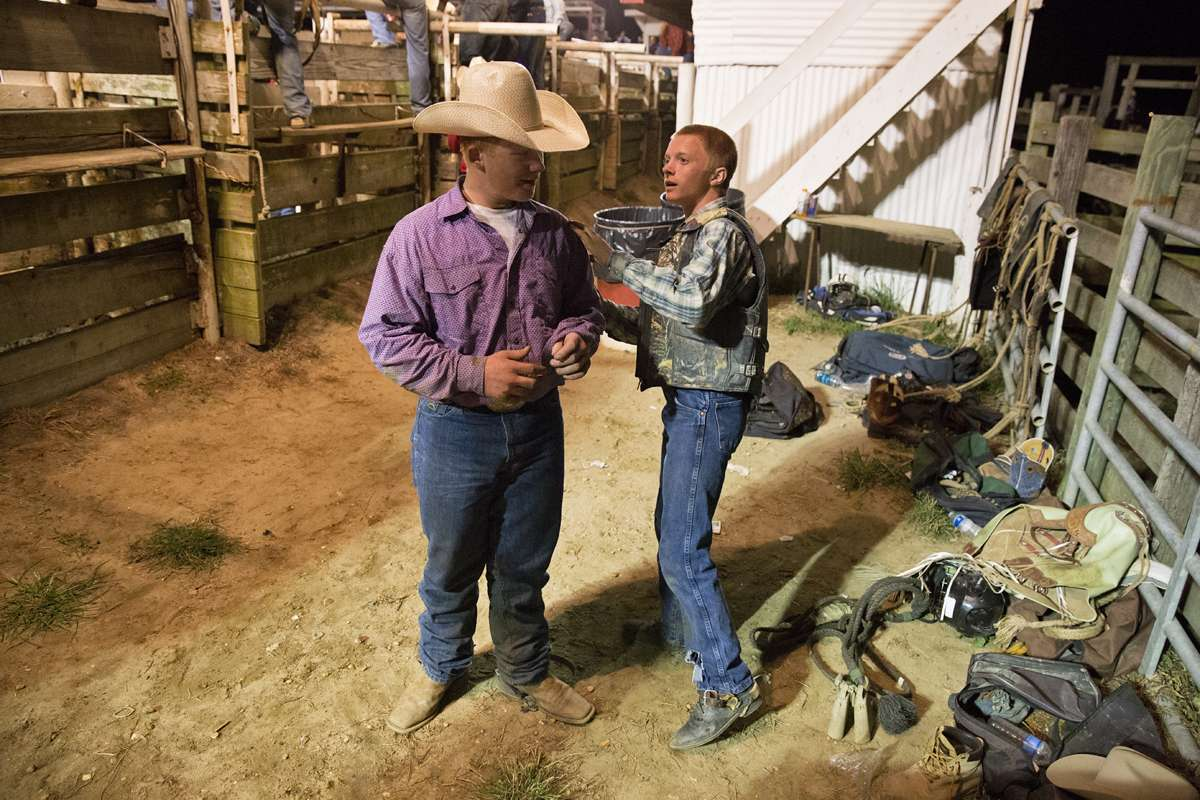 Clay Harp and Parker Ship show each other fresh bumps and scraps from the junior bull riding competition. (Lindsay Lazarski/WHYY)