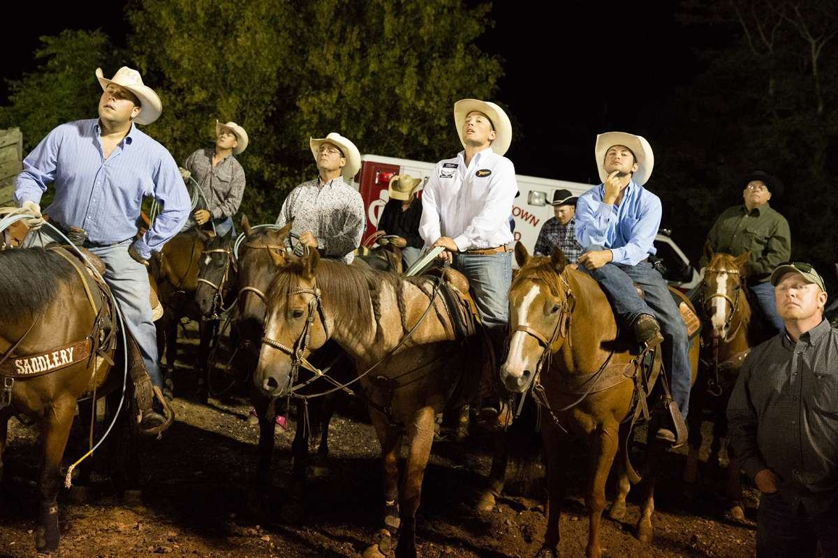 Cowboys look onto the arena from behind the scenes at the Cowtown Rodeo. (Lindsay Lazarski/WHYY)
