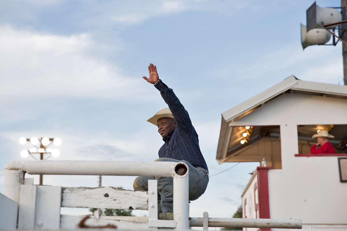 Troy Alexander waves to a fan before the start of the Cowtown Rodeo on a Saturday night in Pilesgrove, New Jersey. (Lindsay Lazarski/WHYY)