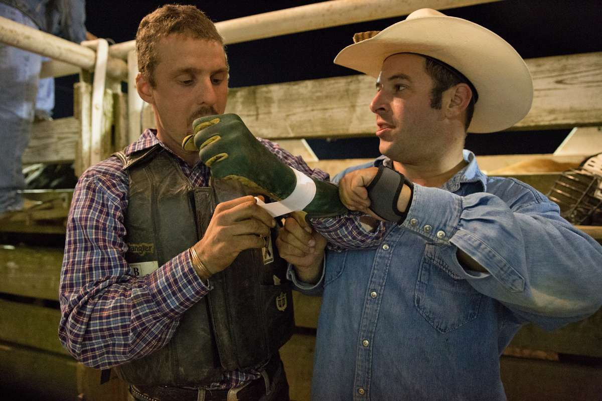 Bareback rider Jim Elchak helps bull rider Nat Brenize tape his gloves. (Lindsay Lazarski/WHYY)