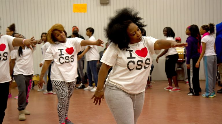 Tawanda Jones leads the Camden Sophisticated Sisters step team through a series of warm up exercises. (Lindsay Lazarski/WHYY)