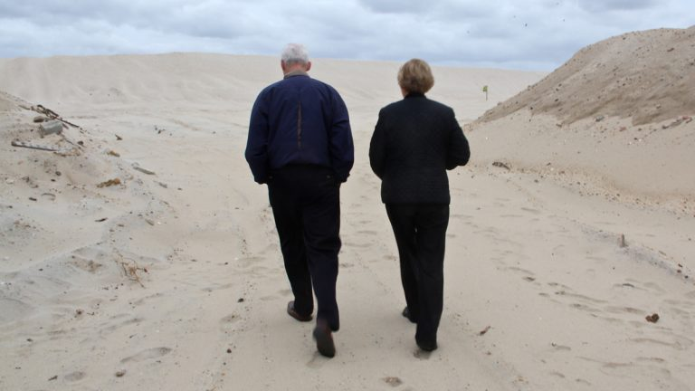 John and Mary Jane Malone walk through Camp Osborn, once crowded with tiny vacation bungalows. (Emma Lee/for NewsWorks)