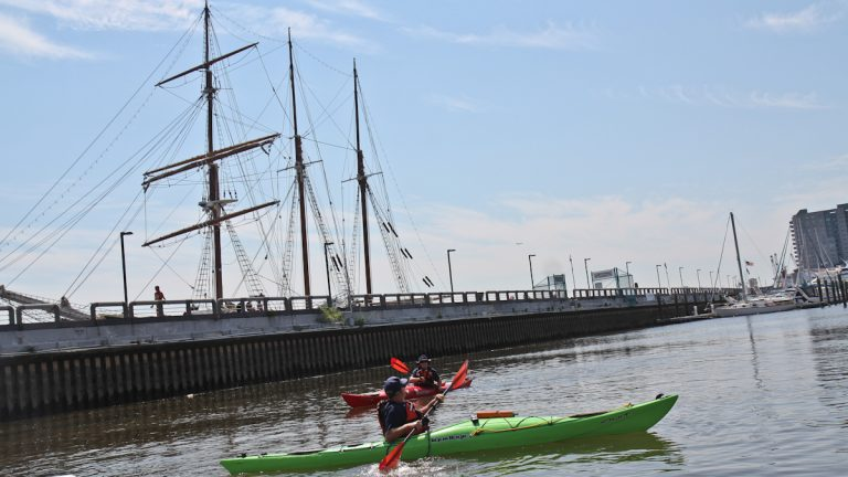 Joseph Smith and Laurie Huselton with the Coast Guard Auxiliary paddle on the Delaware River near Penn's Landing. (Kimberly Paynter/WHYY)