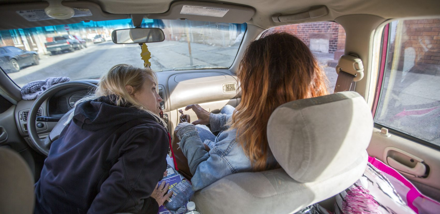 Carol Rostucher (left) and Barb Burns ride through the Kensington neighborhood of Philadelphia doing outreach to the homeless and those struggling with addiction. Rostucher started the non-profit Angels in Motion. (Jessica Kourkounis/For Keystone Crossroads)