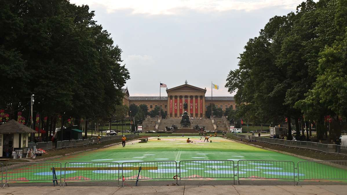 Painters work to turn Eakins Oval into a magic carpet Sunday evening. The official opening event is Wednesday July 16th. (Kimberly Paynter/WHYY)