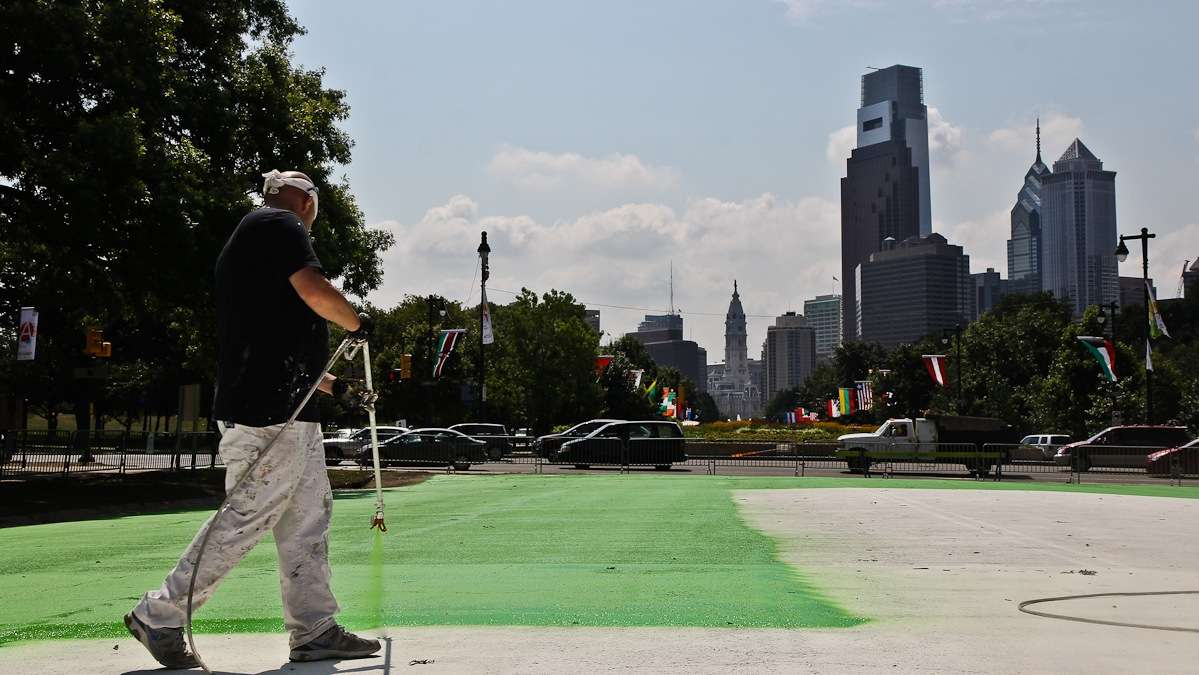 Howard Stokes spray paints the Eakins Oval parking lot Friday. He calls the neon colors 'wild.' (Kimberly Paynter/WHYY)
