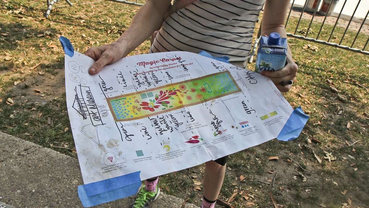 Artist Candy Coated holds the plans for turning Eakins Oval into a magic carpet. (Kimberly Paynter/WHYY)