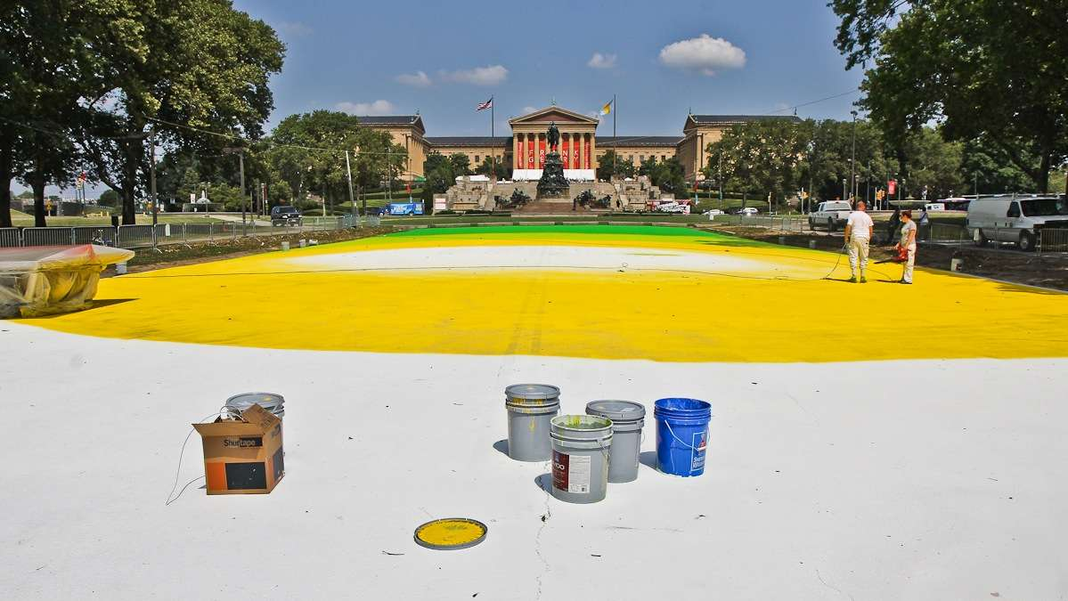 Painters begin to turn Eakins Oval on the Parkway into a magic carept Friday morning. (Kimberly Paynter/WHYY)
