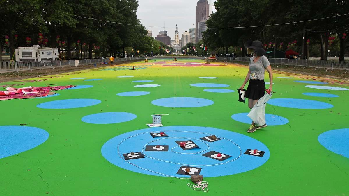 Artist Candy Coated lays out a hopscotch game on the Eakins Oval magic carpet. (Kimberly Paynter/WHYY)