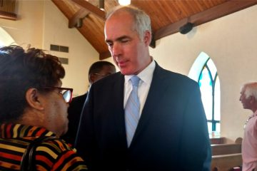 U.S. Sen. Bob Casey, D-Pennsylvania, speaks with a constituent at Bethel AME Church in Ardmore Monday. Casey is reintroducing a bill that would ban those convicted of misdemeanor hate crimes from buying firearms. (Katie Colaneri/WHYY)